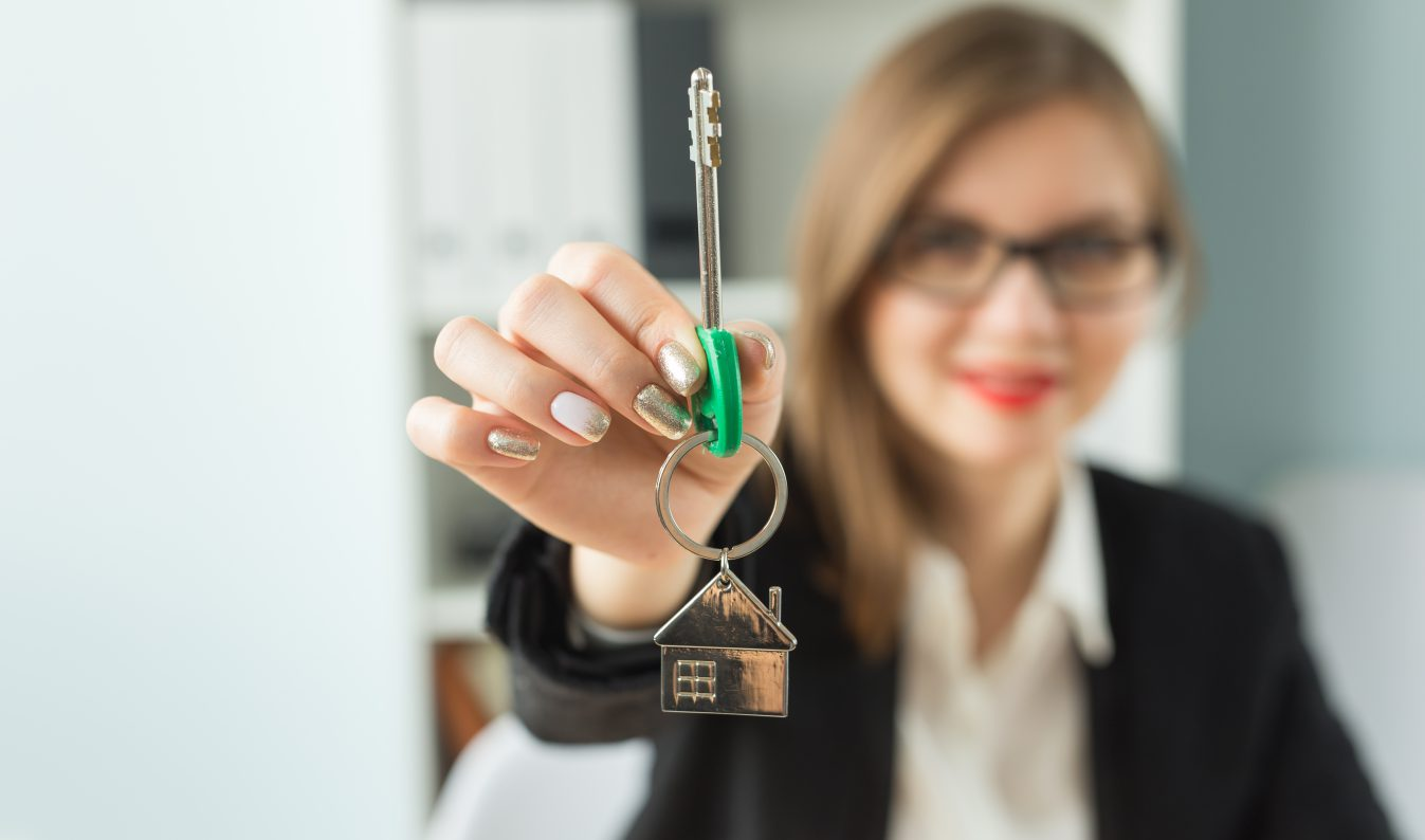 New home and real estate concept - Close up of happy realtor woman with red lips giving you keys from new apartment